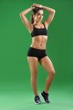 Красивая спортсменка представляя на зеленой предпосылке Стоковое Фото
