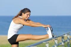 Красивая спортсменка протягивая с морем на заднем плане Стоковое Фото