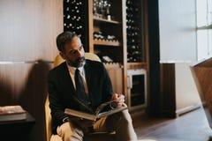 Красивая средн-постаретая книга чтения бизнесмена на софе Стоковое фото RF
