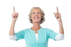 Красивая старшая дама указывая вверх Стоковая Фотография