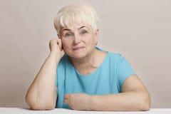 Красивая старшая белокурая женщина в голубом платье стоковая фотография rf