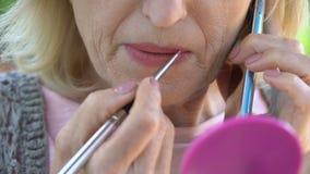 Красивая старшая дама крася ее губы, аранжируя встречу телефоном, женственность видеоматериал
