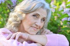 Красивая старшая женщина представляя около зацветая дерева стоковое изображение rf