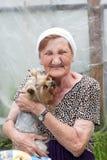 Красивая старшая женщина с ее собакой в саде лета стоковая фотография