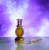 Красивая стеклянная косметическая бутылка дух на предпосылке сирени блестящей Стоковое Изображение