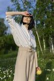 Красивая стильная девушка нося ультрамодную белую рубашку, бежевое trous стоковая фотография