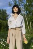 Красивая стильная девушка нося ультрамодную белую рубашку, бежевое trous стоковые изображения