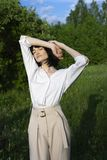 Красивая стильная девушка нося ультрамодную белую рубашку, бежевое trous стоковая фотография rf