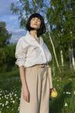 Красивая стильная девушка нося ультрамодную белую рубашку, бежевое trous стоковое фото