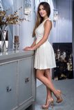 Красивая стильная девушка представляя в внутренней студии Женщина стоит около стильного, современного комода ящиков Стоковая Фотография