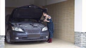 Красивая стильная женщина в длинном платье ремонтирует мотор роскошного автомобиля сток-видео