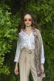 Красивая стильная маленькая девочка нося ультрамодную белую рубашку, бежевую стоковое фото rf