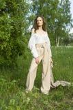 Красивая стильная маленькая девочка нося ультрамодную белую рубашку, бежевую стоковое изображение