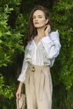 Красивая стильная маленькая девочка нося ультрамодную белую рубашку, бежевую стоковые фото