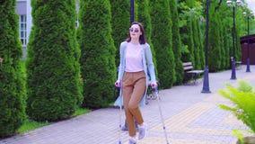 Красивая стильная положительная молодая женщина с ушибом на костылях идя вниз по улице солнечный медленный mo сток-видео