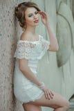 Красивая стильная девушка представляя вкратце белое платье против предпосылки каменной стены Стоковые Изображения RF