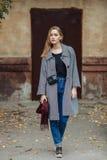 Красивая стильная молодая женщина в ботинках голубых джинсов теплых шарфа ультрамодных и уютном пальто представляя самостоятельно Стоковое Изображение RF