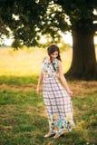 Красивая стойка девушки около большого зеленого дерева любовная история девушки сада мальчика целуя Стоковое фото RF