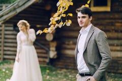 Красивая стойка groom на дальше запачканной предпосылке невесты Свадьба осени outdoors Стоковые Изображения