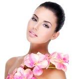 Красивая сторона женщины с здоровой кожей и розовыми цветками Стоковые Изображения RF