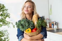 Красивая сумка посещения магазина бакалеи молодой женщины с овощами дома Стоковые Фотографии RF