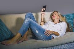 Красивая счастливая белокурая женщина предыдущее 40s ослабила дома живущую комнату используя средства массовой информации интерне стоковые фото