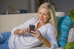 Красивая счастливая белокурая женщина предыдущее 40s ослабила дома живущую комнату используя средства массовой информации интерне стоковые изображения