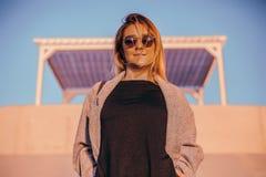 Красивая счастливая женщина в солнечных очках стоя на море, девушка в сером пальто Стоковая Фотография RF