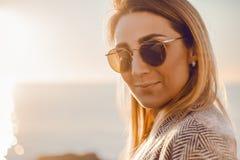 Красивая счастливая женщина в солнечных очках стоя на море, девушка в сером пальто Стоковые Фотографии RF