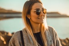 Красивая счастливая женщина в солнечных очках стоя на море, девушка в сером пальто Стоковое Изображение