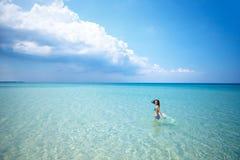 Красивая счастливая женщина стоя в купальнике на голубом море стоковое изображение
