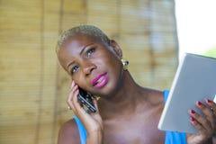 Красивая счастливая и занятая черная афро американская женщина работая на кофейне говоря на сети мобильного телефона на цифровой  Стоковая Фотография