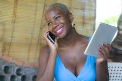 Красивая счастливая и занятая черная афро американская женщина работая на кофейне говоря на сети мобильного телефона на цифровой  Стоковые Фото