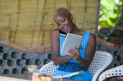 Красивая счастливая и занятая черная афро американская женщина работая на кофейне говоря на сети мобильного телефона на цифровой  Стоковые Изображения RF