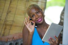 Красивая счастливая и занятая черная афро американская женщина работая на кофейне говоря на сети мобильного телефона на цифровой  Стоковые Изображения