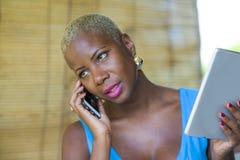 Красивая счастливая и занятая черная афро американская женщина работая на кофейне говоря на сети мобильного телефона на цифровой  Стоковые Фотографии RF