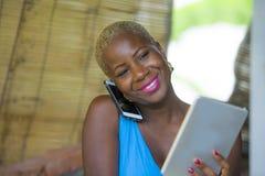 Красивая счастливая и занятая черная афро американская женщина работая на кофейне говоря на сети мобильного телефона на цифровой  Стоковое Изображение
