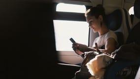 Красивая счастливая кавказская девушка связывая при друзья используя smartphone и усмехающся пока путешествующ на поезде видеоматериал