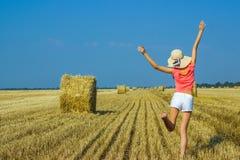 Красивая счастливая маленькая девочка скача для утехи в воздухе около стога сена стоковое изображение rf