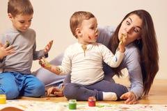 Красивая счастливая мать и ее 2 маленьких сынов одетых в домашних одеждах сидят на деревянном поле в комнате и стоковые фотографии rf