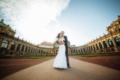 Красивая счастливая пара свадьбы целует outdoors на предпосылке улицы города Стоковая Фотография RF