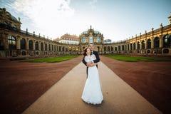 Красивая счастливая пара свадьбы целует outdoors на предпосылке улицы города Стоковые Фото
