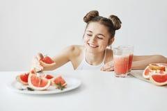 Красивая счастливая девушка усмехаясь принимающ кусок грейпфрута от плиты сидя на таблице над белой стеной Здоровый фитнес Стоковые Фото