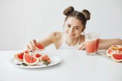 Красивая счастливая девушка усмехаясь принимающ кусок грейпфрута от плиты сидя на таблице над белой стеной Здоровый фитнес Стоковое фото RF