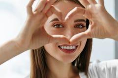 Красивая счастливая женщина показывая знак влюбленности близко наблюдает стоковая фотография rf