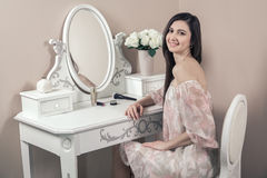 Красивая счастливая женщина с розовым платьем и длинными черными волосами в ее комнате около ее таблицы шлихты представляя перед  Стоковое Фото