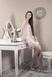 Красивая счастливая женщина с розовым платьем и длинными черными волосами в ее комнате около ее таблицы шлихты представляя перед  Стоковое Изображение RF