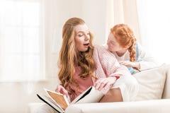 Красивая счастливая книга чтения матери и дочери и усмехаясь один другого дома Стоковые Фото