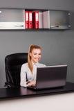 Красивая, счастливая коммерсантка печатая на компьтер-книжке на ее столе Стоковые Фотографии RF