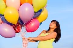 Красивая счастливая молодая девушка беременной женщины outdoors с воздушными шарами Стоковое фото RF